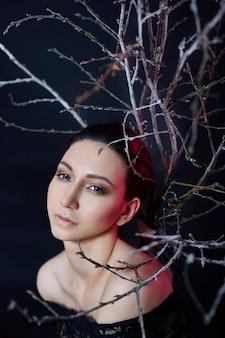 大きな青い目と後ろに枝があるアルメニアの女性の神秘的な肖像画。イブニングドレスでポーズをとる素敵なゴージャスな女の子。明るいメイク