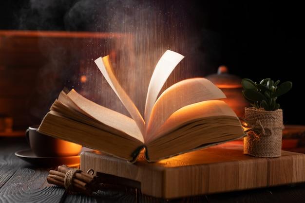 魔法の本のある神秘的な静物、霧が本の上に昇る。本の中のテキストは読めません