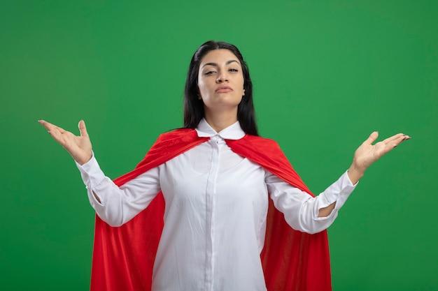 Misteriosa giovane ragazza caucasica del supereroe che mostra le mani vuote con la faccia seria isolata sulla parete verde