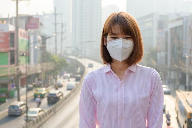 アジアの女性が道路での大気汚染とバンコクの交通に対してn 95呼吸保護マスクを着ています。