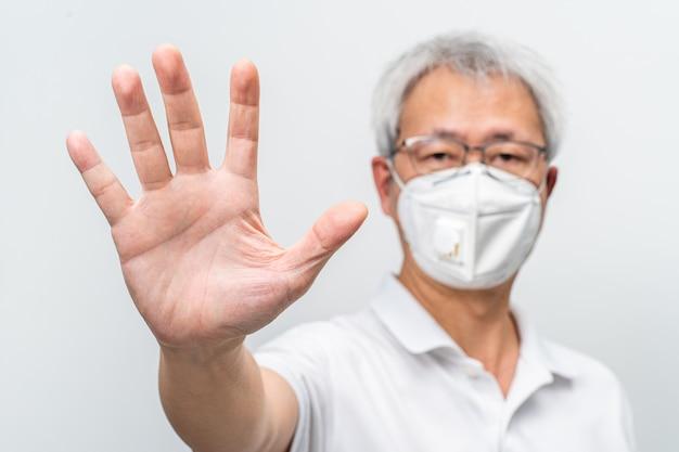 Пожилой мужчина в маске n95 протягивает руку, вытянув ладонь, чтобы остановить вирус covid-19