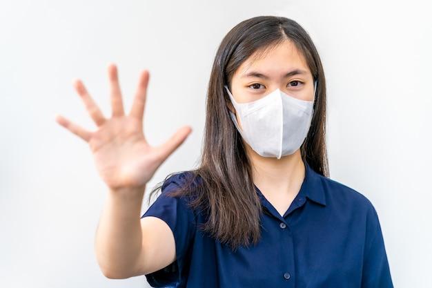 Молодая азиатская девушка-подросток в маске n95 и подняла руку, чтобы остановить вирус covid-19