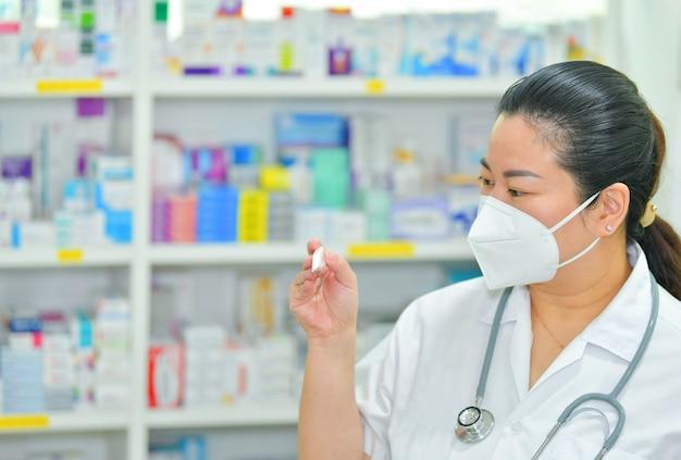 薬剤師は、多くの薬棚の背景に温度計と聴診器でn95マスクを着ています。コロナウイルス(covid-19)病気、インフルエンザの治療と保護の概念