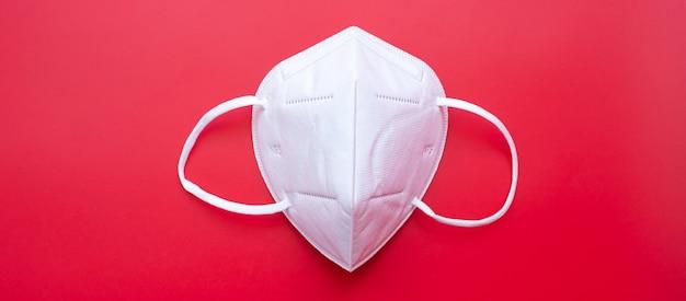 赤い背景のn95呼吸医療用フェイスマスクは、コロナウイルス病(covid-19)とpm2.5(粒子状物質)を防ぎます。