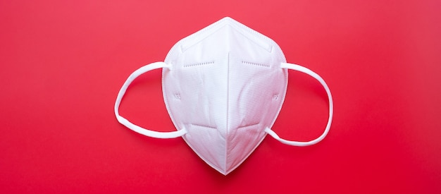 N95 respiratory medical face mask on red background, prevent coronavirus disease (covid-19) and pm2.5 (particulate matter).