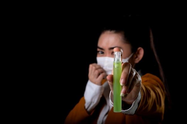 黒の表面での細菌の広がりを防ぐためにペットボトルまたは抗菌剤からアルコールスプレーを適用する手でマスクn95マスクを置く若いアジア女性の実業家