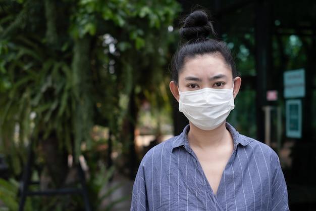 Женщина носит на респираторе маску n95 на открытом воздухе