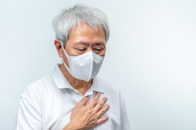 Старый азиатский мужчина в маске n95, положив руку на грудь, чувствует себя плохо