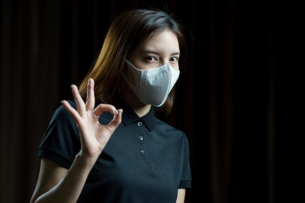 Женщина нося респираторную защитную маску n95 показывая знак руки одобренный.