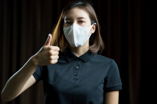 Женщина, носящая респираторную защитную маску n95, показывая руку с большим пальцем вверх.