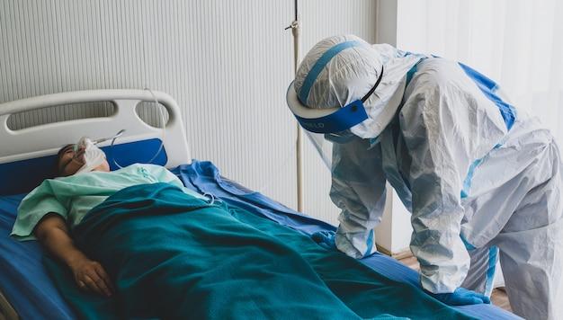 Два азиатских доктора носят сиз костюм с маской n95 и защитной маской, чувствуют усталость и депрессию, когда лечат пациентов с кислородной маской в комнате отрицательного давления.