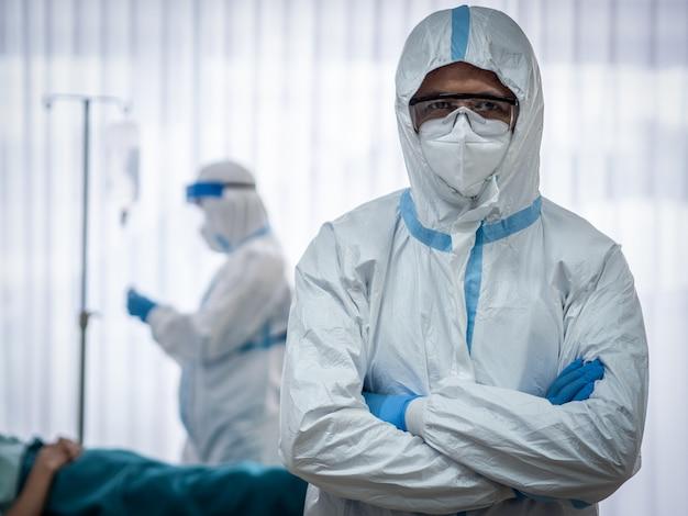 Два азиатских доктора носят сиз костюм с маской n95 и защитной маской, лечат и используют кислородную маску с больным коронавирусом в комнате отрицательного давления.