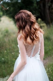 カールn白いウェディングドレス屋外で若いきれいな花嫁、後ろから見る