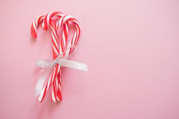 クリスマスとnにグリーティングカードのためのパステルピンクの背景に銀の弓を持つキャンディの杖
