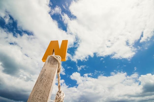 青い雲の空の前に文字n木材