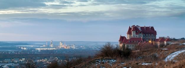 Сиротливый замок здания стоя na górze холма горы и промышленной электростанции oland позади на ноче. город ивано-франковск, украина