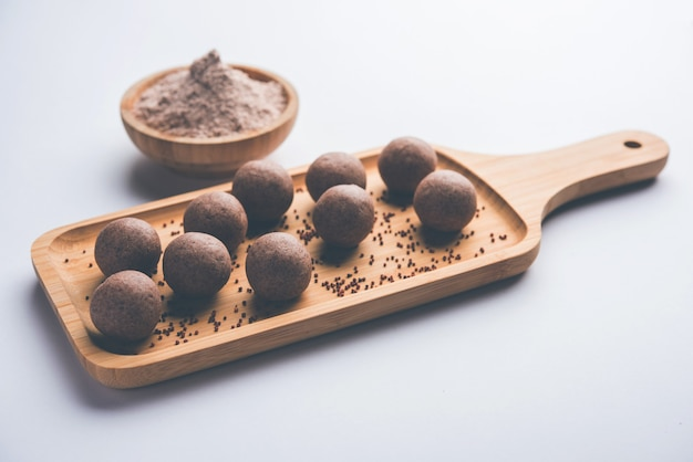 Nachni laddu or ragi laddoo or balls made using  finger millet, sugar and ghee. it's a healthy food from india. served in a bowl or plate with raw whole and powder. selective focus