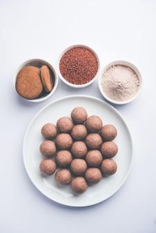 Nachni 또는 ragi laddu 및 손가락 기장, 설탕 및 버터 기름을 사용하여 만든 비스킷 또는 쿠키. 인도에서 온 건강식입니다. 생 전체 및 분말과 함께 그릇이나 접시에 제공