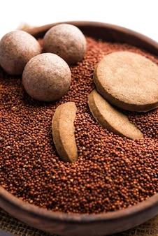 Nachni 또는 ragi laddu 및 비스킷 또는 손가락 기장, 설탕 및 버터 기름을 사용하여 만든 쿠키. 인도에서 온 건강식입니다. 생 전체 및 분말과 함께 그릇이나 접시에 제공