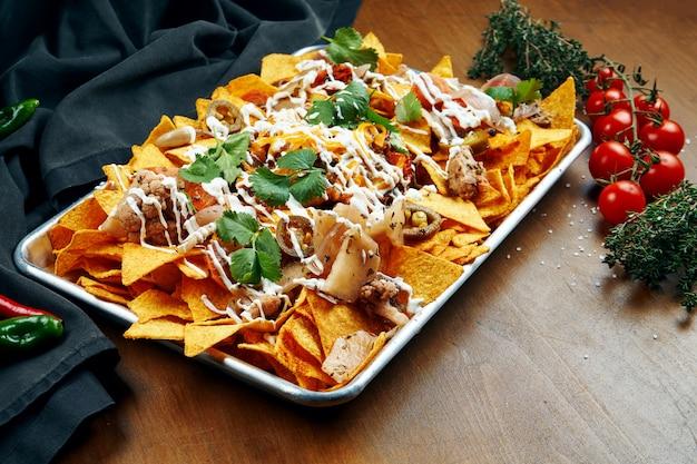 Nachos - классическая мексиканская закуска, приготовленная из кукурузных чипсов. начос с соусами и холопеня. вид сверху. закройте