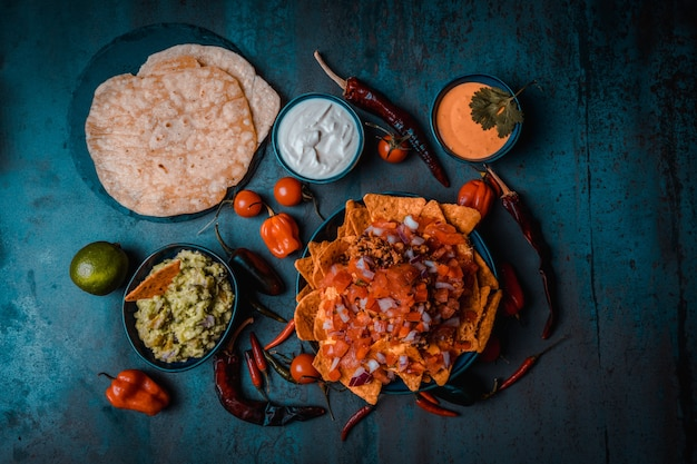 ワカモレサワークリームペッパーとトルティーヤダークフードを添えたメキシコ料理のナチョスとチェダーチーズ