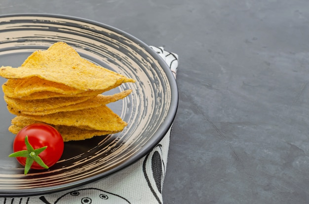 Nachos on a black plate and cherry tomato in the dark table. mexican cuisine. close-up. with copy space.