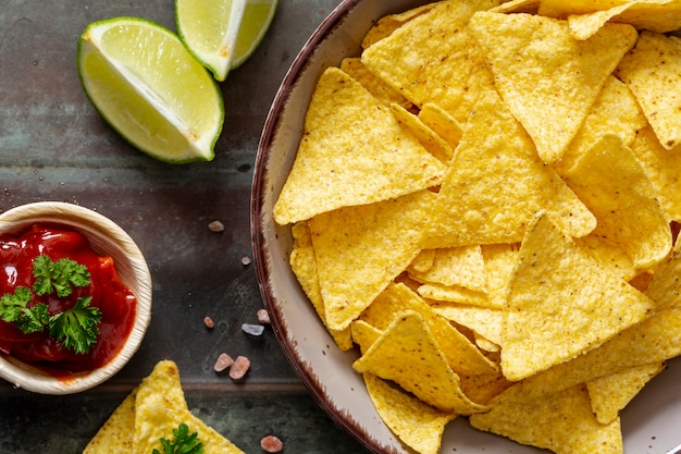 Nachos in bowl, tomato sauce and sliced lime