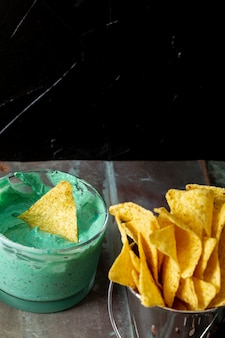 Nachos in bucket and green sauce in bowl on table