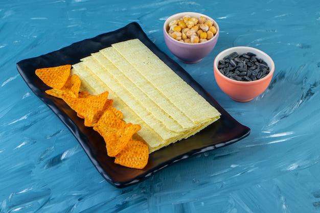 Patatine di nachos e patatine lunghe su un piatto da portata accanto a semi e ceci, sulla superficie blu.
