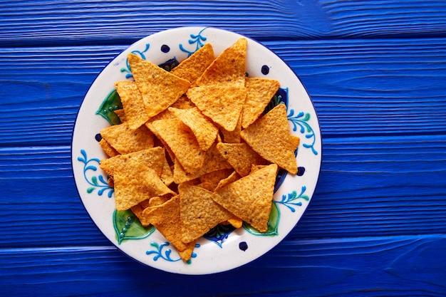 Nachos чипсы на мексиканской тарелке над синим