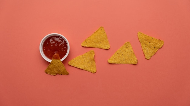 Nachos chips in sauce on a colored background