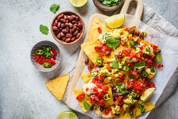 Nachos chips with cheese sauce, guacomole, salsa and vegetables on the board, top view. party food concept.