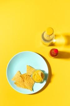 黄色の青いプレートにチーズソースを添えたナチョスチップス