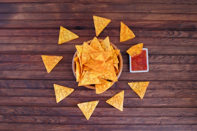 Nachos corn chips in a bowl with spicy sauce on a rustic wooden