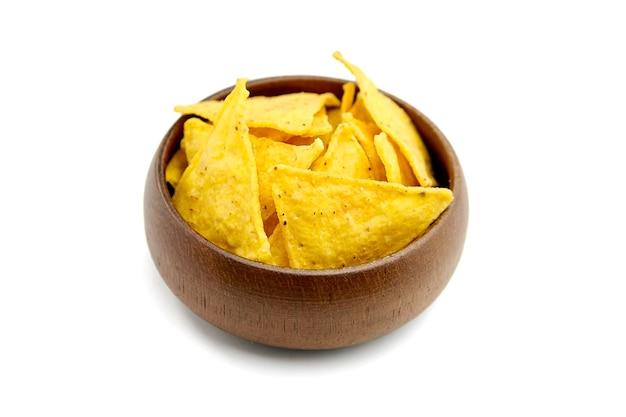 ナチョス、木製のボウルにコーンチップ、白い背景で隔離のスナック。ベジタリアンに適したファーストフード。伝統的なメキシコ料理。セレクティブフォーカス