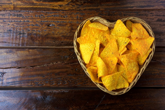 Nachos corn chips placed in basket with heart shape on wooden table, space for text