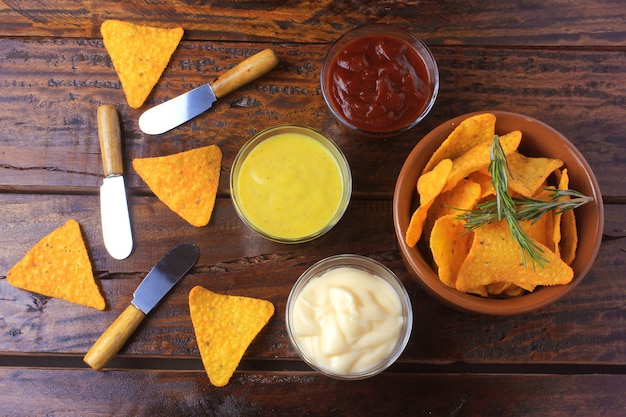Nachos corn chips placed in ceramic bowl on wooden table next to assorted sauces