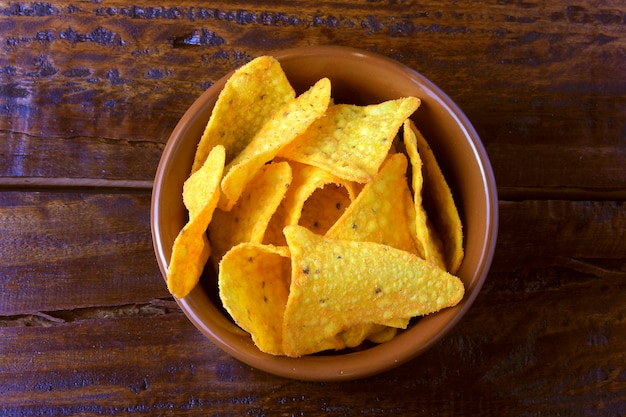 Nachos corn chips placed in ceramic bowl on wooden table, copy space