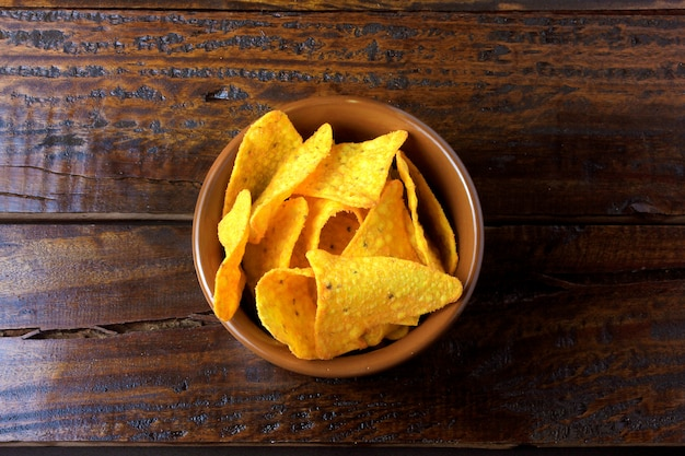 Nachos corn chips placed in ceramic bowl on wooden table