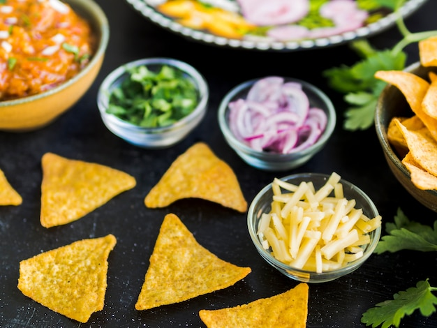 Nachos and cups with vegetables and potatoes