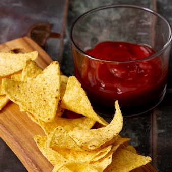 Nachos on cutting wooden board and tomato sauce in bowl