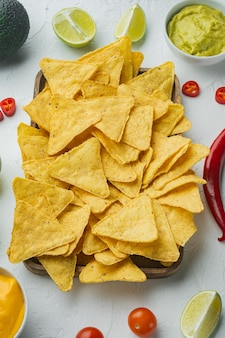 Nachos and guacamole and cheese sauces, on white background