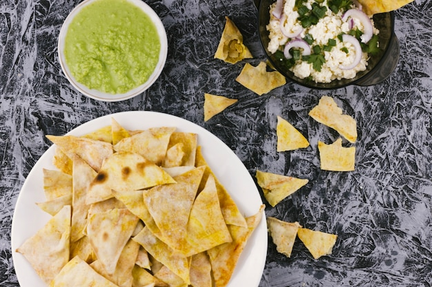 Nachos and guacamole dip on marble background