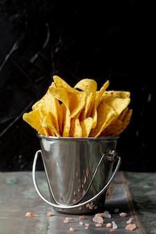 Nachos in metallic bucket against black background
