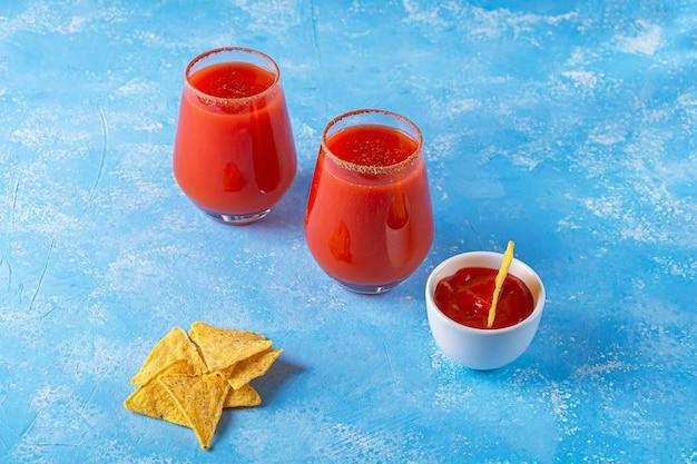 ナチョス、ソース、ミチェラーダのアルコール飲料は、青いテクスチャ背景に2つのグラスで