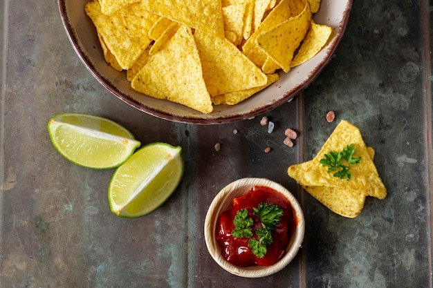 Nachos, tomato sauce in bowl and sliced lime on desk