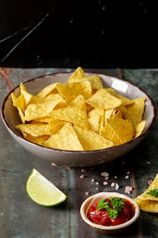 Nachos, tomato sauce and sliced lime on desk against black background