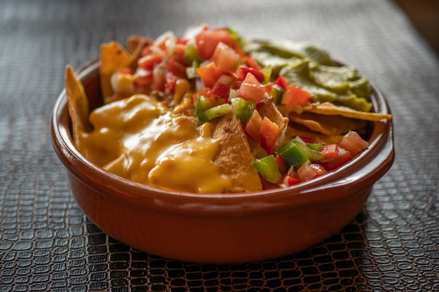 Nachos with cheddar cheese and guacamole in a clay pan on a dark table