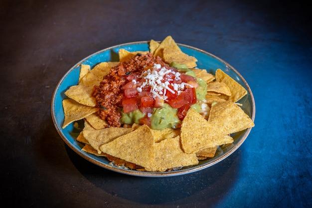 파란색 접시에 검은 배경에 아보카도 소스와 토마토 소스를 곁들인 나초