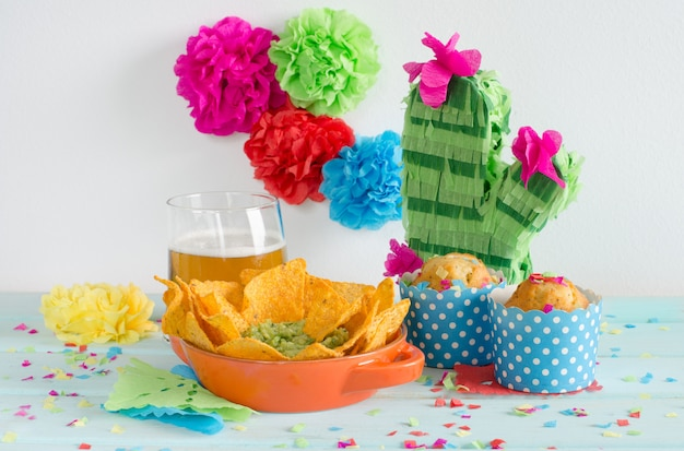 Nachos with guacamole and beer with colorful flowers.